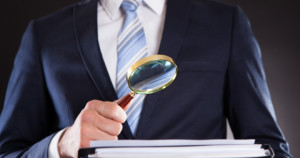Midsection of businessman examining documents with magnifying glass against black background